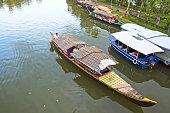 Vembanad Lake, Kumarakom, Kerala/India: A big tourist boat ply in the Kerala backwaters, past the others tourist boast lined on the lush green side walk.