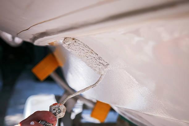 Boat maintenance, applying white toxic paint on boat bottom stock photo