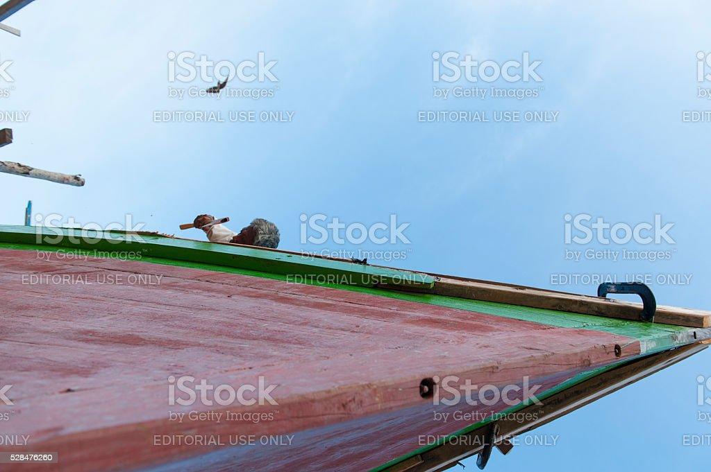 Boat maker repairing the wooden boat in Mabul Island, Malaysia. stock photo