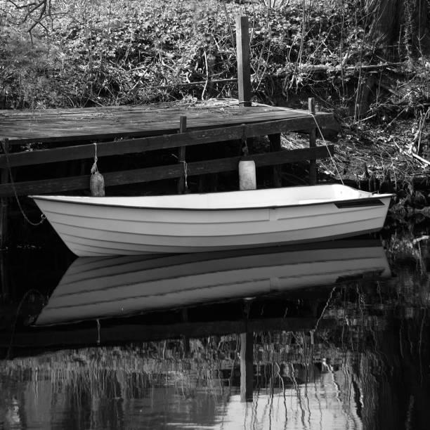 Båten förtöjd av träbro bildbanksfoto