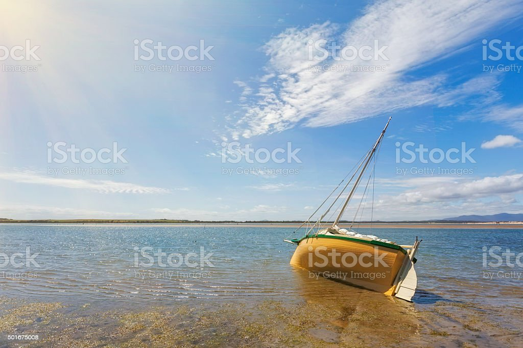 Boat moored on shallow waters of Sandy Point, Australia stock photo