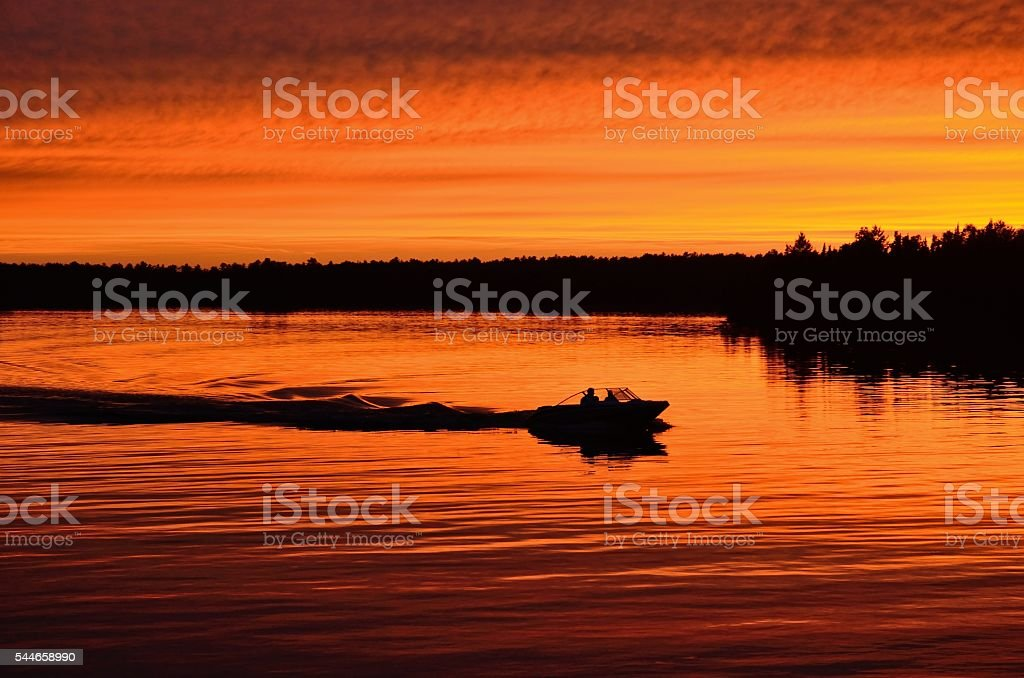 Boat Motoring After Sunset stock photo