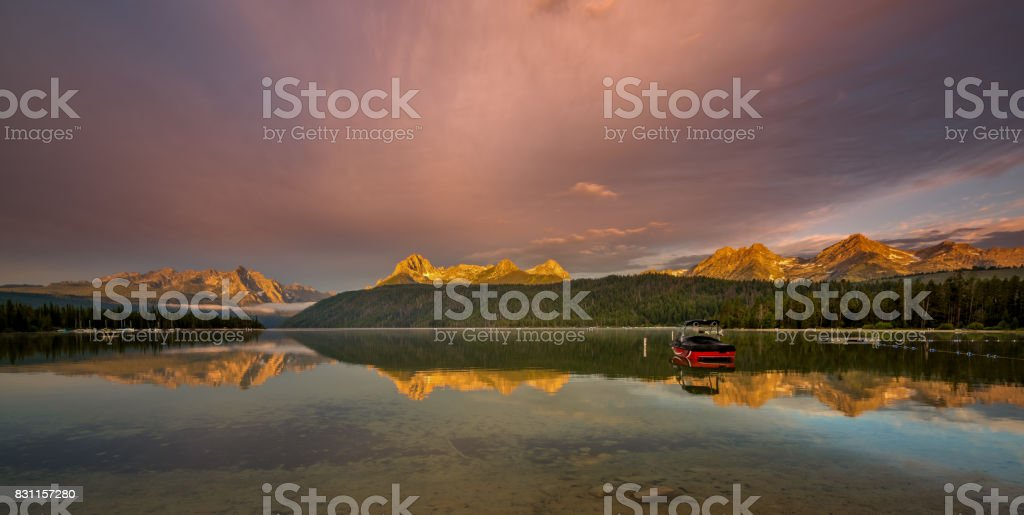 Boat on a lake as the morning light hits the high mountain tops stock photo