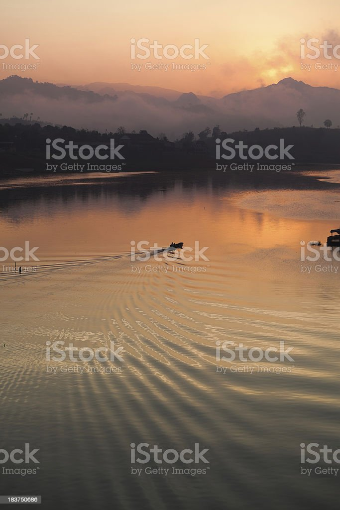 Boat on a Lake at Sunrise in Thailand royalty-free stock photo