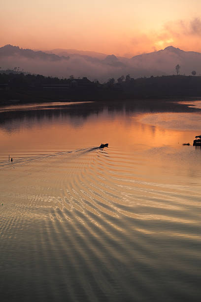 Boat on a Lake at Sunrise in Thailand stock photo