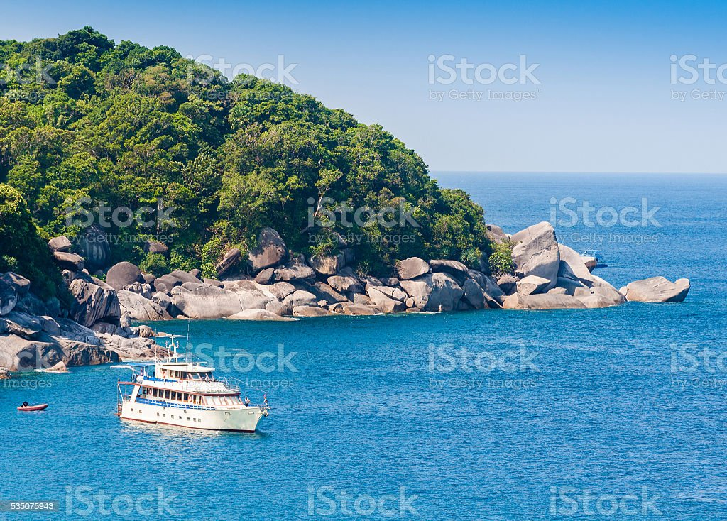 Boat on beautiful sea and tropical island with clear water stock photo