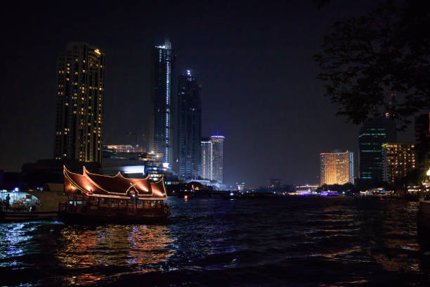 Boat on Chao Phraya River at Night in Bangkok, Thailand stock photo