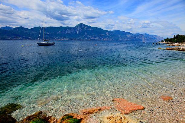boot auf dem idyllischen und türkis gardasee, malcesine-italien - ferienhaus am gardasee stock-fotos und bilder