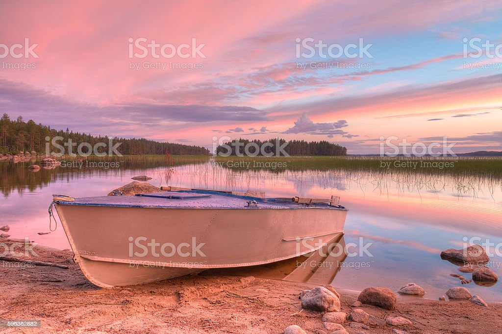 Boat on shore of lake in beautiful evening royalty-free stock photo