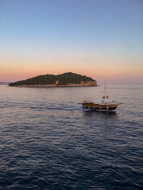 Boat on the Adriatic Sea with Lokrum Island in the Sunset ストックフォト
