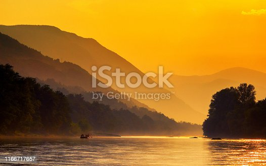 Boat on the river and mountains in the back at summer dusk.