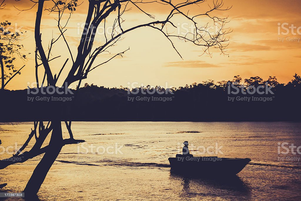 Boat on the River at Sunset in Borneo stock photo