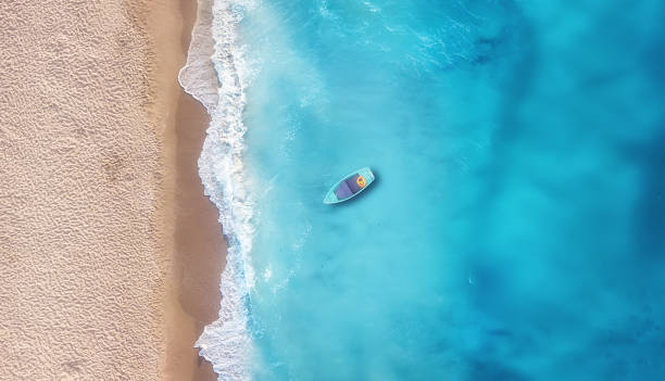 boat on the water surface from top view. turquoise water background from top view. summer seascape from air. travel concept and idea - laguna foto e immagini stock