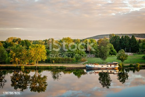 istock Boat on the Yonne river with reflections at sunset near Joigny in Burgundy, France. 1287587820
