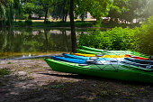 Boat parking on the river bank on a sunny summer day. Rental kayaks, boats in the park.