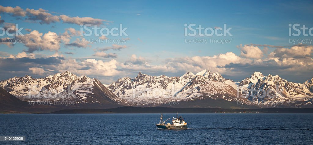 Boat passes before Lyngen Alps northeast of Tromso Norway stock photo