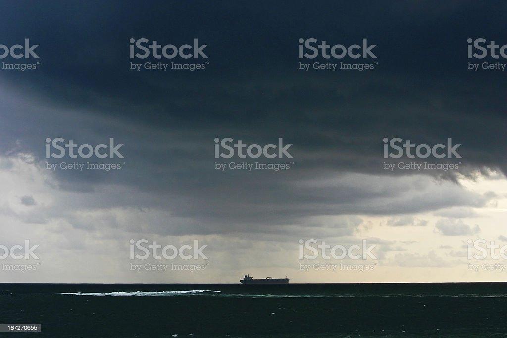 Boat passes through dark clouds stock photo