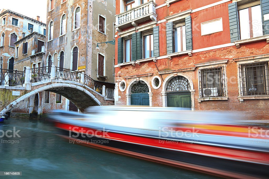 Boat passing by the bridge along a canal in Venice royalty-free stock photo