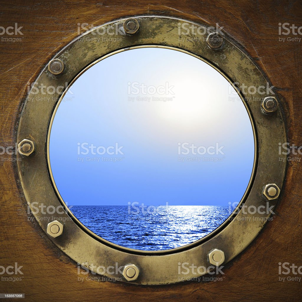 Boat porthole looking at ocean and sky stock photo