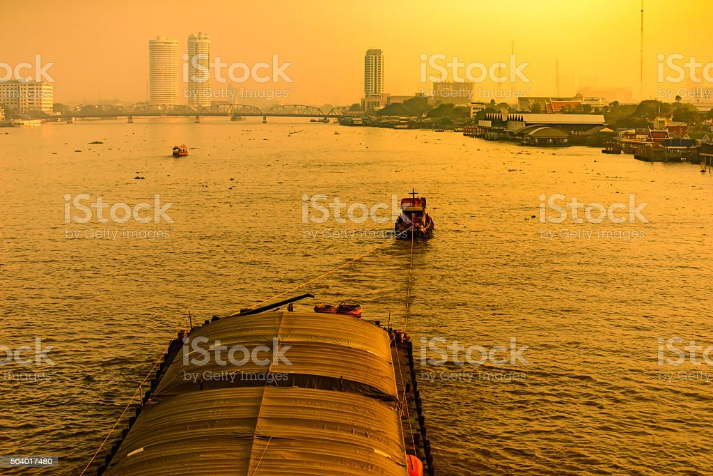 Boat pulled by a tugboat cargo carry the product at the Chaophaya...
