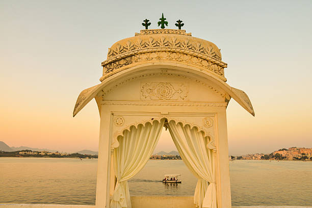 Boat Ride on Lake Pichola Seen in Gazebo, India This is a horizontal, selective focus shot of a boat ride on Lake Pichola seen through a gazebo. This was shot at dusk from Jag Mandir Island in Udaipur, India. The lake shore is seen beyond.  lake pichola stock pictures, royalty-free photos & images