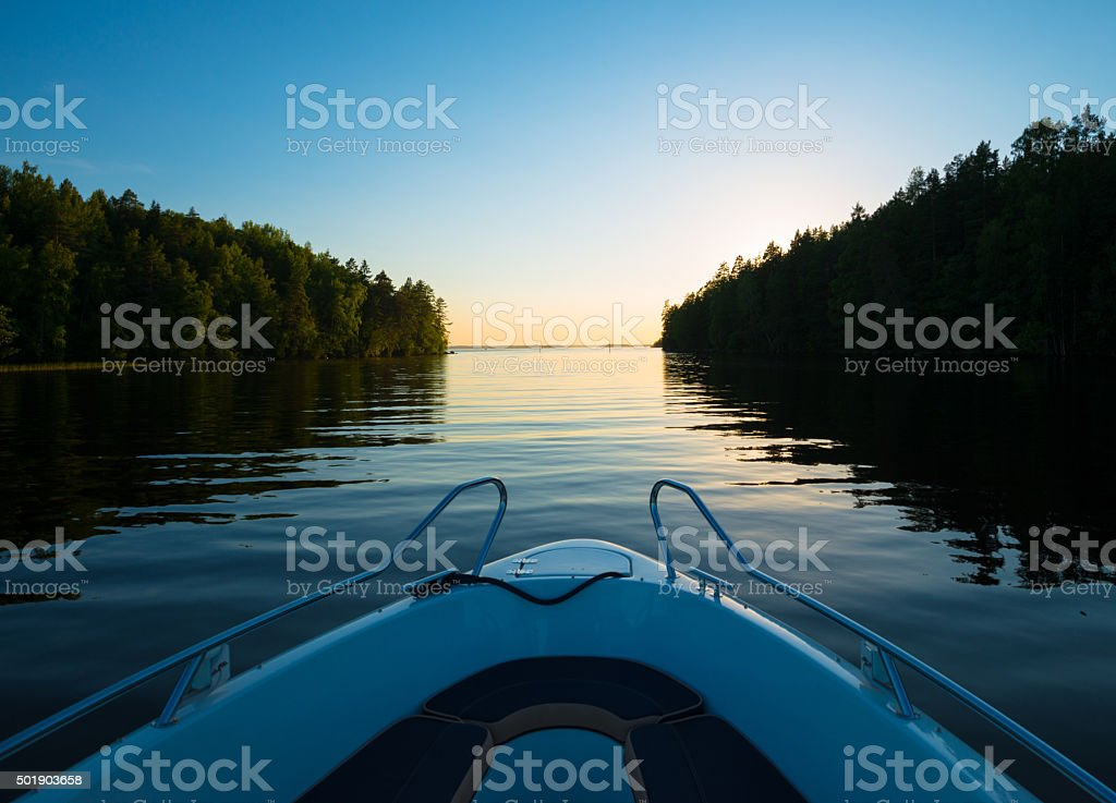 Boat ride through calm canal at sunset stock photo