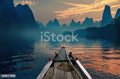 A boat riding in a river during sunset next to a beautiful mountain