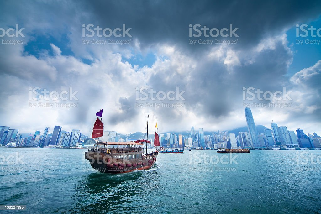A boat sailing against a city skyline stock photo