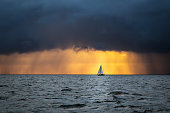 Lonely sailing yacht in the ocean at the approaching storm and raining clouds at sunrise, English channel, near French shores