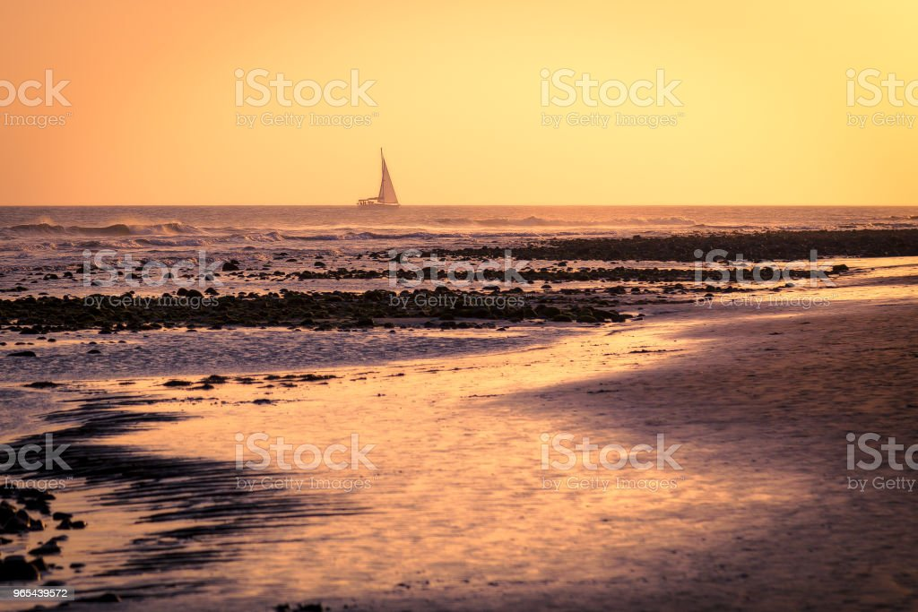 Boat sailing into the sunset royalty-free stock photo