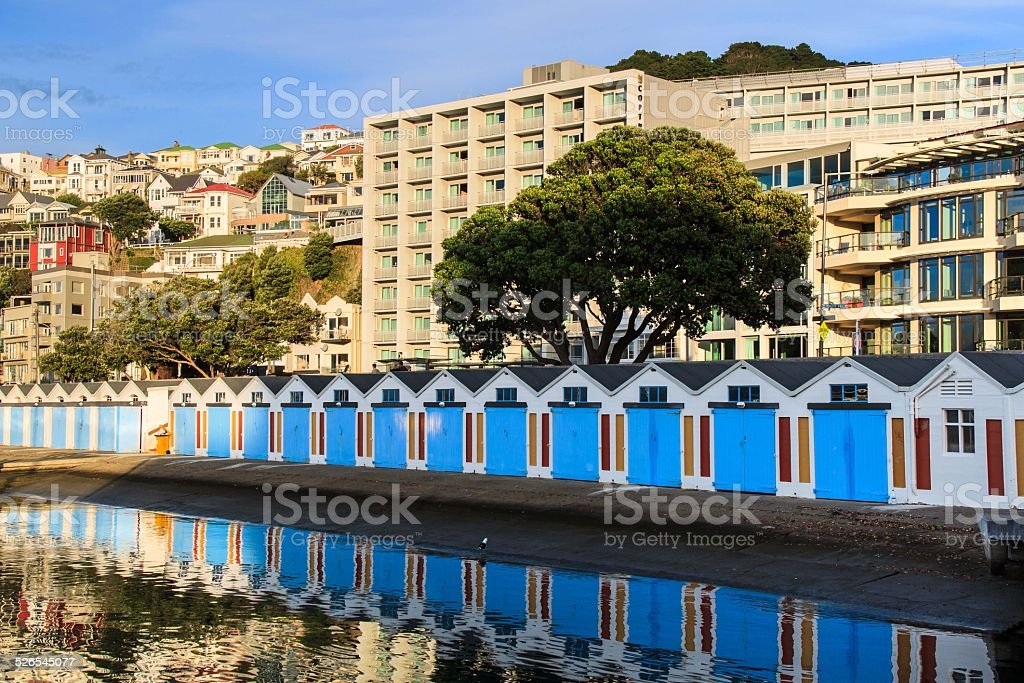 Boat sheds with blue doors with the reflection in water stock photo