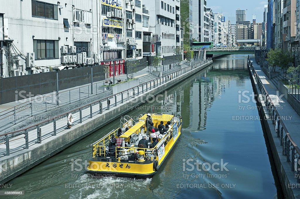 Boat takes tourists along canal in Dotonbori district of Osaka royalty-free stock photo