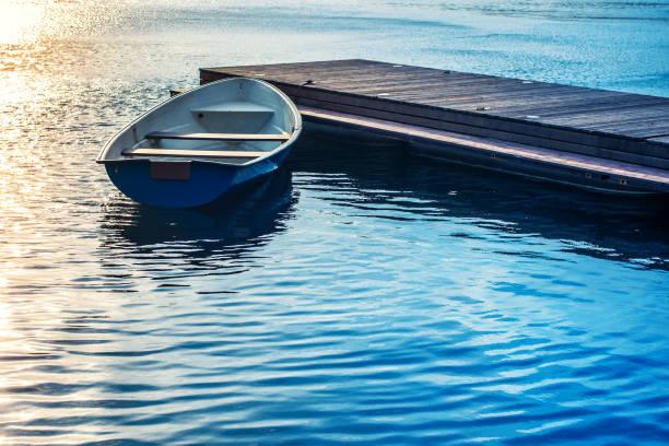 Um barco amarrado a um cais de madeira no lago à noite ao pôr do sol - foto de acervo