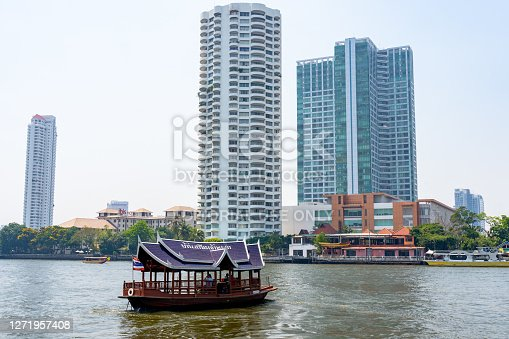 Boat driver service is popular travel on Chao Phraya River. To stay in downtown Bangkok on Memorial Bridge ferry station. Tourist boat decorated with flowers garland