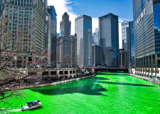 boot fährt neben schatten von gebäuden auf dem chicago river in der nähe von trump tower, die für st. patricks day, grün gefärbt ist, als massen-szene surround werfen. - st. patrick's day stock-fotos und bilder