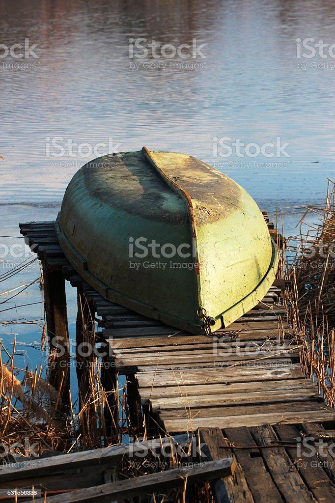 Boat turned upside down lying on shorelake stock photo