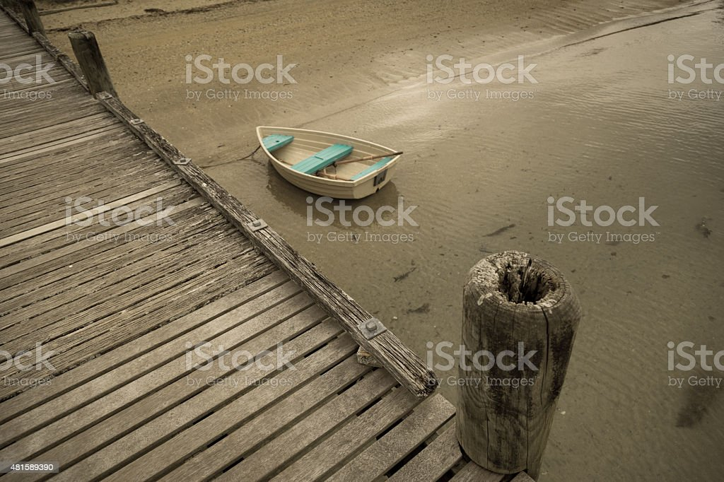 Boat under a wooden pier stock photo