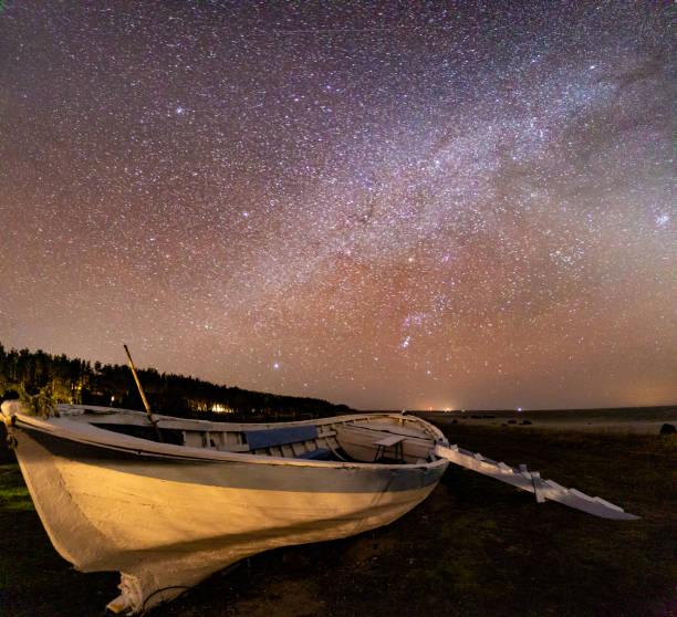 Boat under milky way stock photo