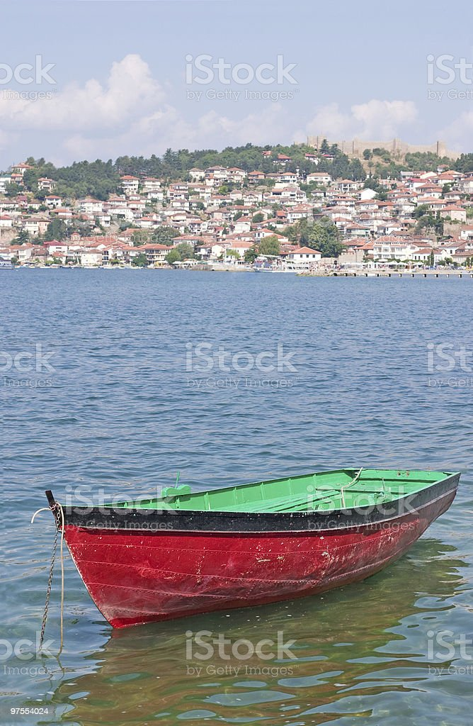 Boat with coast town in background royalty-free stock photo