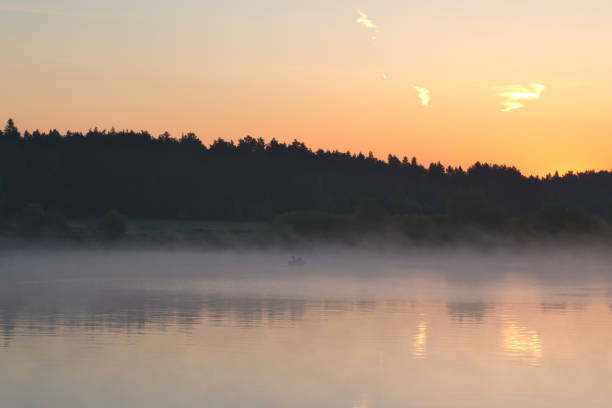 Boat with fishermen in the fog on the river at dawn stock photo