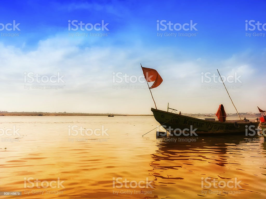 boat with flag in ganga river at banaras india stock photo