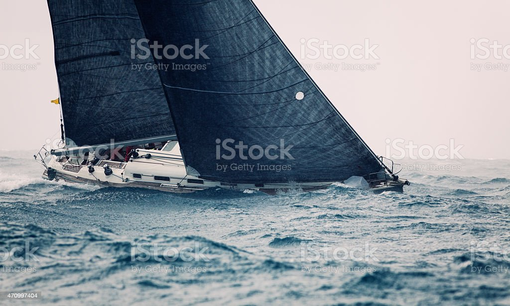 Boat with large black sails on the ocean stock photo