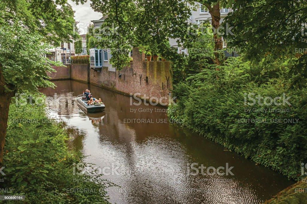 Boot met mensen navigeren de gracht omgeven door muren en weelderige vegetatie in's-Hertogenbosch. foto