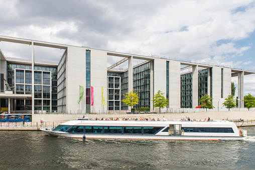 Boat with tourist sailing in the Spree River next to the Marie-Elisabeth-Lüders-Haus building, part of the Bundestag at Berlin city, Germany.