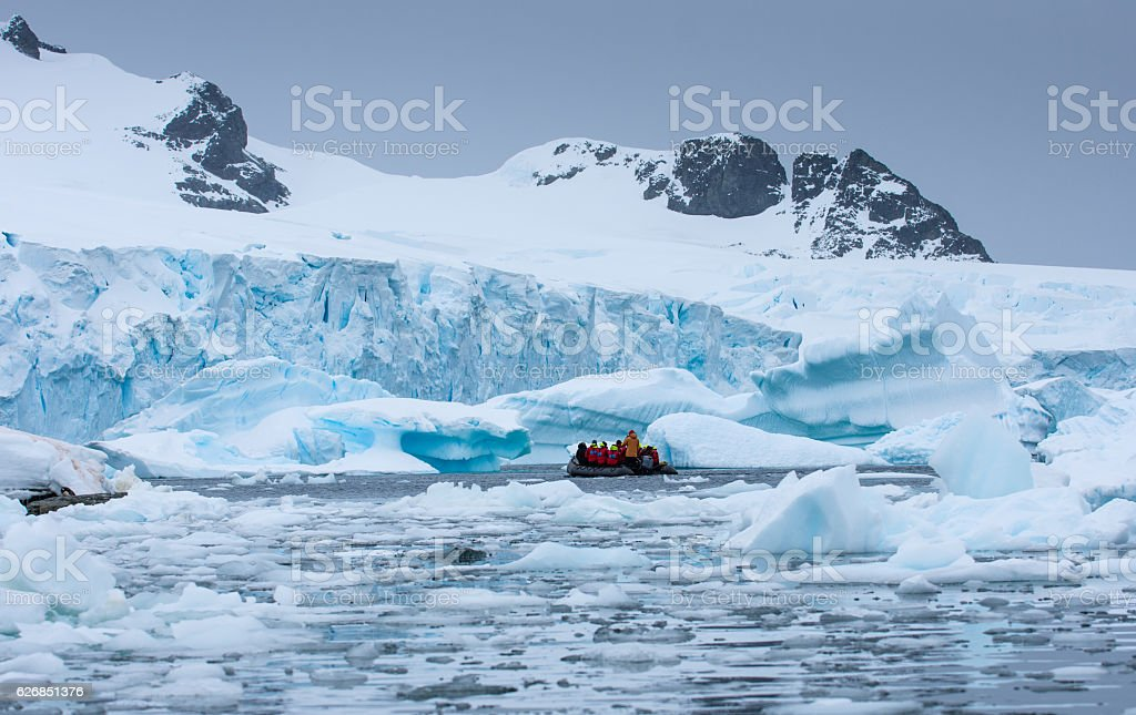Boat with tourists floating amongst Icebergs in Antarctica stock photo