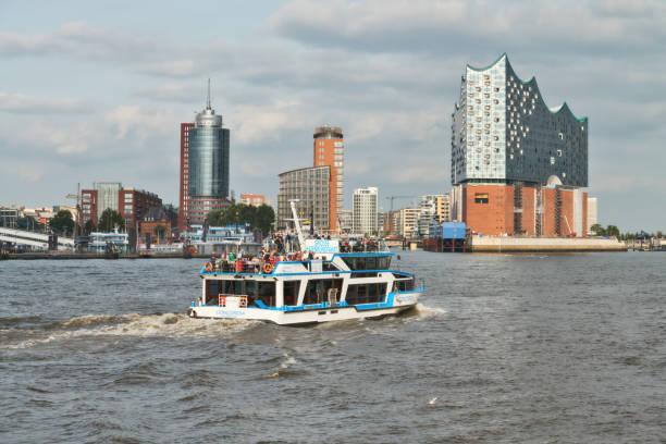 boat with tourists goes on elbe river towards elbphilharmonie in hamburg - hotel stadt hamburg stock-fotos und bilder