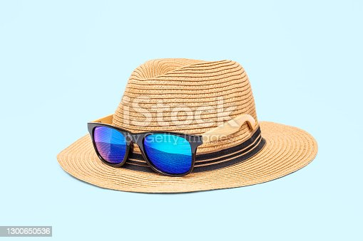 Boater straw hat with sunglasses isolated shot in the Studio. Concept of fashion clothing accessories and beach holidays