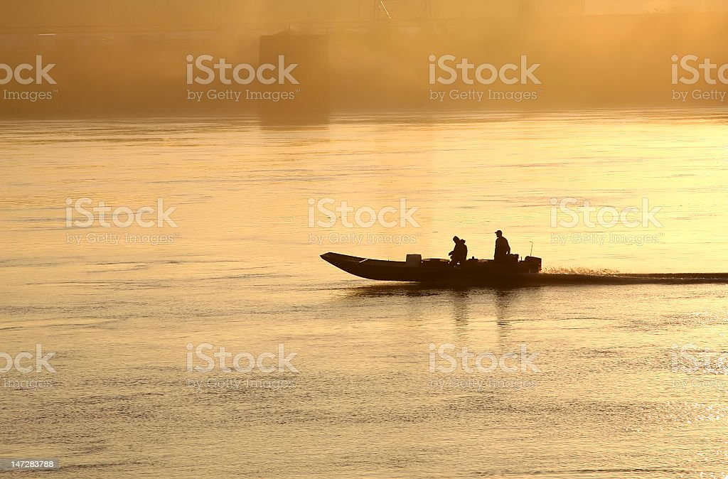 Boaters on River at Dawn royalty-free stock photo
