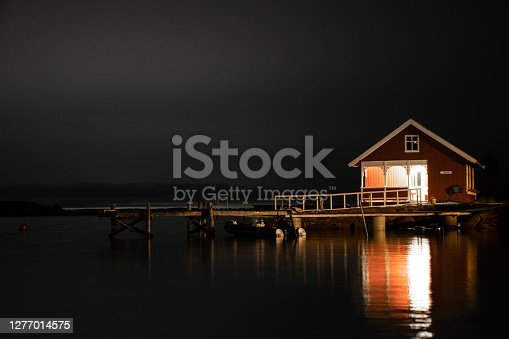 An old boat house sitting by the water at night, with one light at the porch
