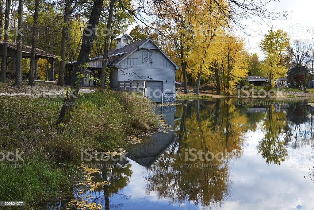 Boathouse with Fall Trees and Reflection in the Water stock photo